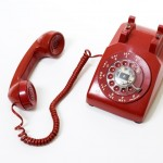 isolated old style red phone off the hook on white